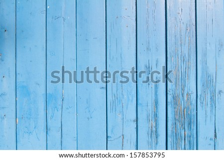 light blue painted planks of old shed with peeling paint