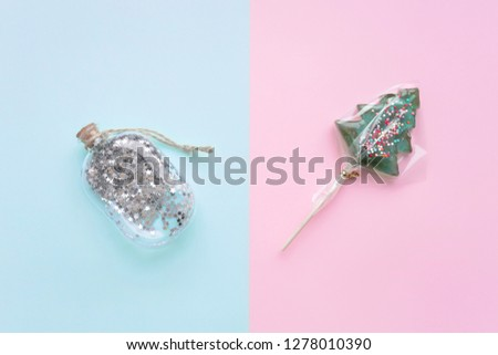 Light blue pink background tree toy and candy stars glitter bottle cork rope. Christmas sweets mood decorate. Flatlay.