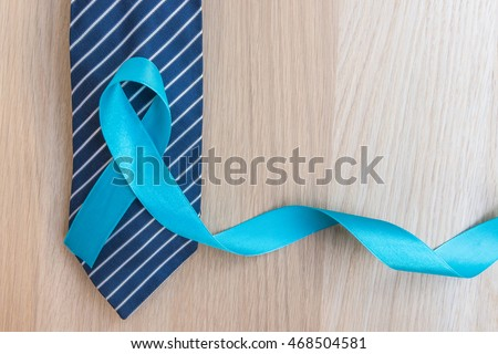 Light blue ribbon symbolic sign for prostate cancer awareness campaign and men\'s health in November and September on necktie & wood background: Shiny blue satin texture textile on wooden backdrop