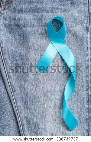 Light blue ribbon symbolic sign for prostate cancer awareness campaign/ concept and men\'s health promotion in November on Jeans denim background: Shiny blue ribbon texture textile on Jeans backdrop