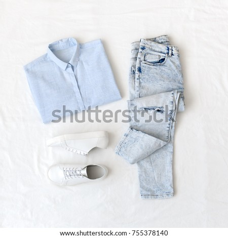 Light blue shirt, ripped boyfriend jeans and white lace up sneakers lying on the white sheet. Overhead view of woman's casual day outfits. Trendy hipster look.