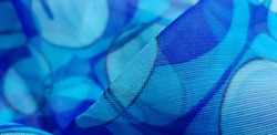 Light blue, translucent fabric with geometric print of small circles; in folds (texture).