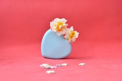 light blue vase in the shape of a heart with daffodils.  Valentine's Day background