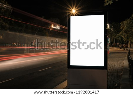 Light box display with white blank space for advertisement. Mock-up design concept with beautiful car light trails at night. Long exposure.