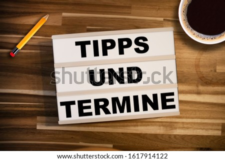 Light box or lightbox on a wooden tablet with the german words for tip and dates upcoming events - Tipps und Termine