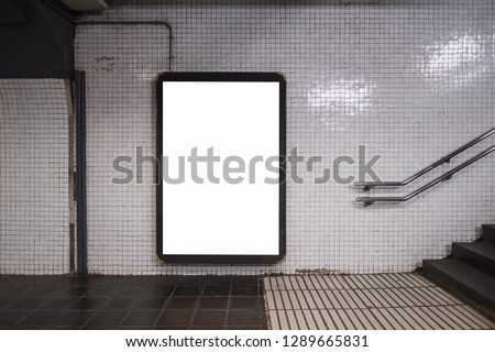 Light box screen with white blank space for advertisement and hand railings to the right. Subway mock-up concept for commercial purposes.