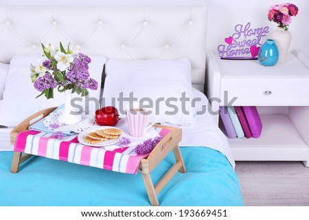 Light breakfast and beautiful bouquet on bed