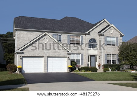 Light brick home in suburbs with double arched garage