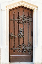 Light brown, antique wooden doors with carvings and patterns. Metal handles made of gold. A semicircular vault. Entrance to the house.