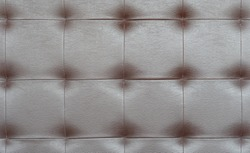 Light brown luxury upholstery sofa texture background concept for clean gray vintage leather furniture pattern wallpaper, closeup interior elegant armchair mattress surface detail, real tuft material.