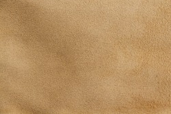 Light brown suede leather texture close up. Useful as a background for project work.