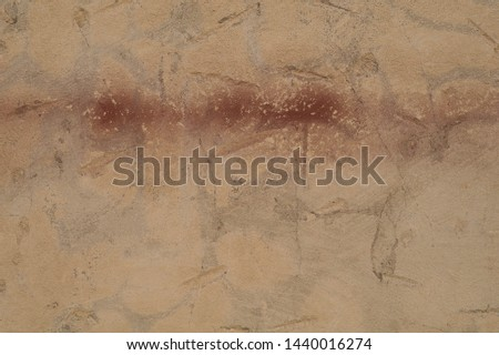 Light brown vintage background texture. Old light brown cement sand plaster with an interesting pattern of nicks with an ax. A rough crackedwall. At the top of the image is a wide red horizontal trail #1440016274