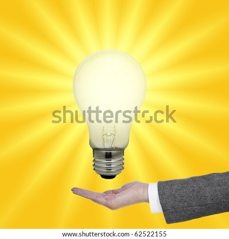 Light bulb above palm - stock photo