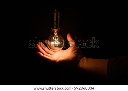 Light bulb and hand, concept of wisdom. #592960334
