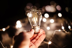 light bulb filament idea background. Energy lamp filament. Invention idea. Hand holding light bulb