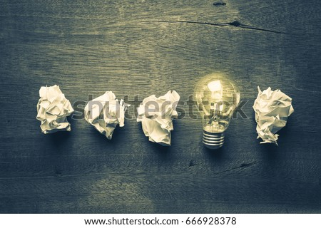 Light bulb glowing in a row of crumpled ball paper, learning from mistake