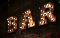Light bulb glowing letter. Text for your desing. Inscription  Neon lit 'BAR' sign on brick wall light banner.
