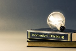 Light bulb glowing on the Innovative Thinking book