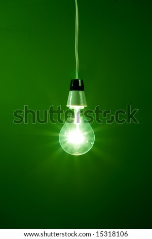 Light bulb hanging against green background