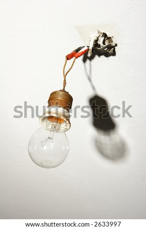 light bulb hanging from bare wires with shadow