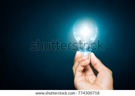 light bulb hold in hand on blue background