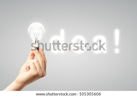light bulb in hand and word idea on gray background