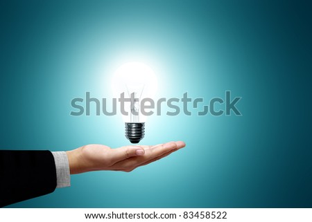Light bulb in hand business woman on green background