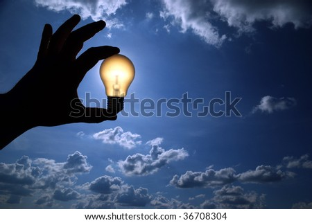 light bulb in the hand on sky background