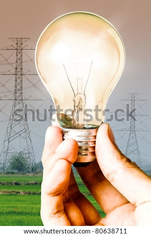 Light bulb in the hand with electricity post background, Save energy and power concept