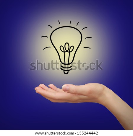 Light bulb in woman hand on blue background