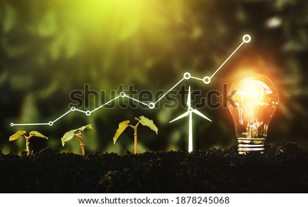 Light bulb is located on the soil, and plant are growing with wind turbine. Renewable energy generation is essential in the future. Alternative sources of energy. Green energy, eco energy concept.
