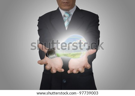 Light bulb of Energy in hand business man on grey background