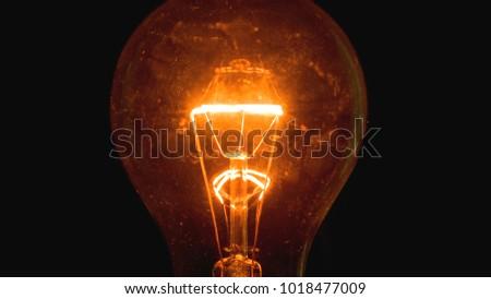 Light bulb on a black background #1018477009
