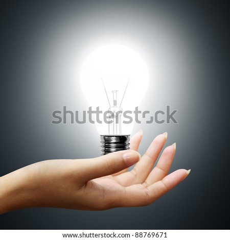 light bulb on business hands on gray background