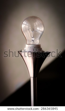 Light bulb on reflective, metallic stand, with soft backround Bulb is switched off.