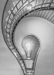 light bulb shaped cubism staircase in historical building in the centre of old Prague in black and white