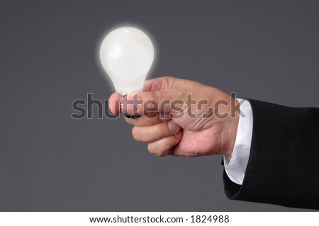 Light bulb shinning at hand with neutral background