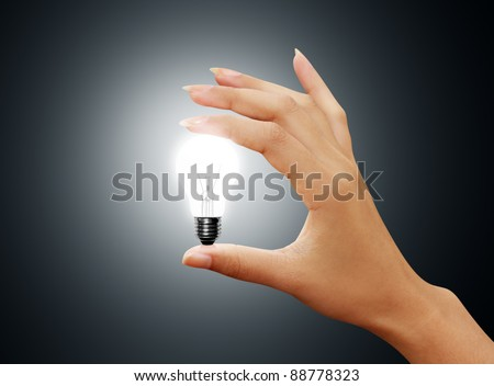 light bulb small on woman hand on gray background