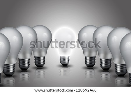 Light bulb turn on in middle of the other light bulbs. Concept for outstanding person, key person in business company - stock photo