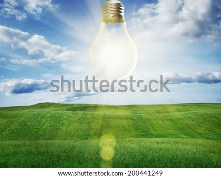 Light bulb with a sunshine inside in field. Environment, eco technology and solar energy concept.