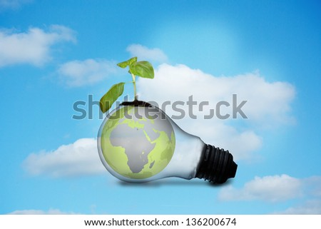 Light bulb with plant and earth against sky background