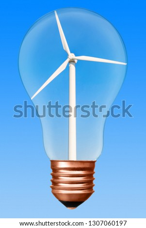 Light bulb with wind turbine inside on a blue gradient background. Conceptual picture