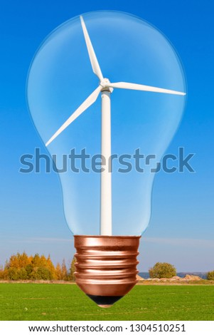 Light bulb with wind turbine inside on the background of blue sky and green field. Conceptual picture