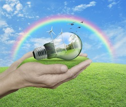 Light bulb with wind turbines, birds and forest inside in hands over green grass with blue sky, clouds, and rainbow, Ecological concept