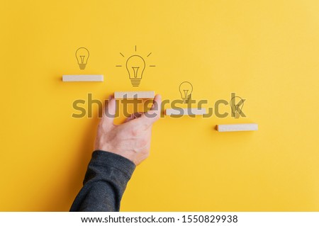 Light bulbs drawn above each step in conceptual stairway of wooden pegs with male hand supporting the one with the biggest and glowing bulb.