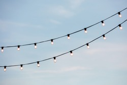light bulbs garlands on a background of blue sky. Christmas lighting in the afternoon.