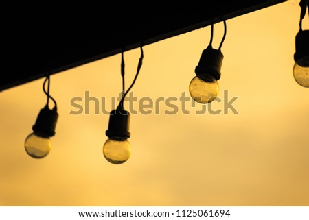Light bulbs on string wire against sunset sky background.Lamp string hanging.Thailand #1125061694