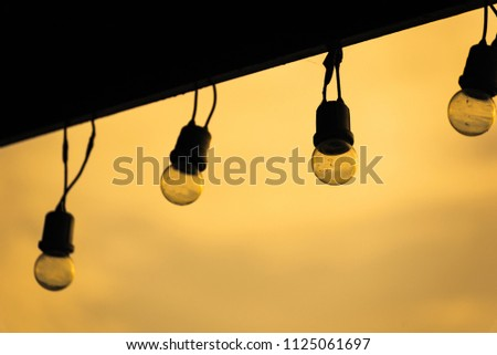 Light bulbs on string wire against sunset sky background.Lamp string hanging.Thailand #1125061697