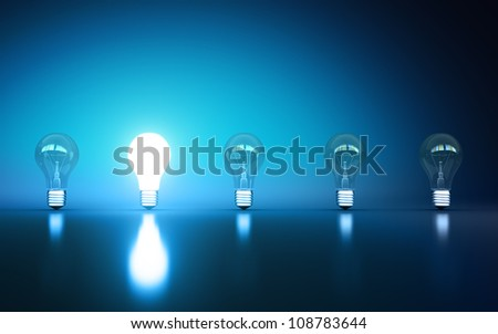 light bulbs stand in rows one glows on a blue background
