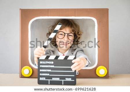 Photo of  Light, camera, action! Child playing with cardboard box TV. Kid having fun at home. Video blogging concept